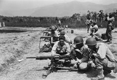 Men of the 147th Infantry Regiment learning how to fire a captured Japanese Nambu machine gun on a heavy weapons range, photographed on New Caledonia Island (November 24, 1944). In the background, others train on American M1917 .30 caliber machine guns.