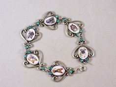 I finally received the vintage Swarovski crystals I ordered for this setting and they are fabulous!  They really set it off!  I now have the crystals in acqua marine, amethyst and clear.  The bracelet can hold up to 6 different fur babies.  As with all my designs, I make it featuring digital portraits of your fur baby. It is $22.99 including shipping.  www.simplyitalydesigns.com