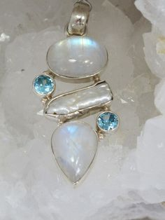 Two highly iridescent cabachon Sri Lankan Rainbow Moonstone gemstones with 2 round faceted London Blue Topaz accent stones and one Biwa Pearl, set in 925-hallmarked sterling silver. Total pendant leng