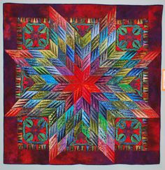 """Cosmic Rhapsody by Ronald Bedard: """"The unusual lone star (a wonderful Karen Stone pattern) went through several color variations; I finally used the color wheel to finalize the scheme"""".  Triadic scheme: blue-red, chartreuse, cerulean blue"""