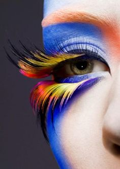 Peacock-inspired makeup with cobalt blue, flaming orange and golden yellow and peach overlay.
