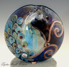 """Peacock Lampwork Focal Bead, 1"""" Lentil by Lydia Muell."""