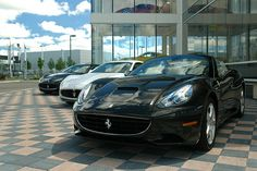 Ferrari California, with two Maserati Granturismos behind it. And, for good measure, a Ferrari 599 GTB Fiorano and and F40 in the showroom behind them.     Awesome