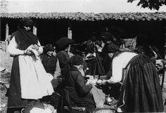 Mulleres con saias escuras fruncidas, mandís claros de liño, mantóns de la merina, negros.