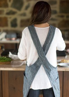 This cleverly crafted apron features a criss-cross back detail that allows it to rest securely on your shoulders. No strings attached! And its roomy, thoughtfully designed pockets are made from the arm cut-outs to reduce fabric waste. Sewing Hacks, Sewing Crafts, Sewing Projects, Modern Aprons, Apron Pattern Free, Japanese Apron, Pinafore Apron, Apron Designs, Sewing Aprons