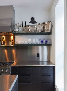 stainless steel kitchen with leather-wrapped, dark green open shelving