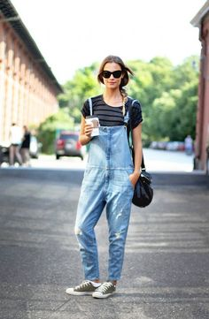 A striped t-shirt is worn with loose overalls, sneakers, and a shoulder bag