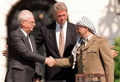 Shot on the White House lawn, this Gary Hershorn photo shows old enemies Rabin and Arafat shaking hands in front of a smiling, wide armed, President Clinton, upon the signing of the Oslo Peace Accord on September 13, 1993.