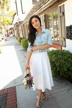 An elegant woman is wearing a white midi skirt and a button-down denim shirt. Pair these two items together for an unexpectedly elegant daytime look. Modest Outfits, Modest Fashion, Skirt Outfits, Skirt Fashion, Fashion Outfits, Fashion Moda, Trendy Fashion, Trendy Style, Style Fashion