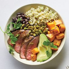 Peruvian Steak and Roasted Sweet Potato Bowl | This is a riff on the Korean rice dish bibimbap, in which various toppings are arranged over a bed of rice. Here, Peruvian steak bowl must-haves such as thinly sliced peeled avocado, roasted sweet potato, and grilled flank steak top brown rice.
