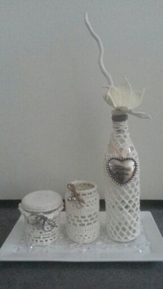 Crocheted bottle and jars all off white coloured, placed on a porcelain plate.