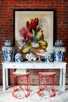 love the bright reddish wire stools with mirrored tops paired with the blue and white ginger jars and white console table