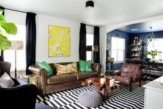 Guests walk right into Taylor and Alisha's vibrant living room, set for entertaining; they love to host! The wood slab coffee table is vintage from the '70s. The leather Chair is '70s vintage Percival Lafer-inspired. The tapestry pillow is custom.
