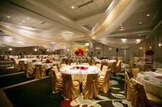 Stunning gold and red wedding reception, with beautiful ceiling draping.