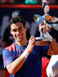 Italy's Fabio Fognini celebrates with the trophy after he won the final match of the bet-at-home ATP tennis tournament against Argentina's Frederico Delbonis in Hamburg, Germany Sunday July 21, 2013. (AP)