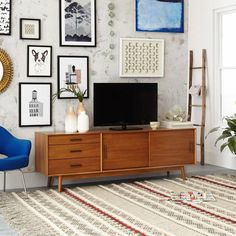 A gallery wall and a mid-century media console make for the perfect retro living room