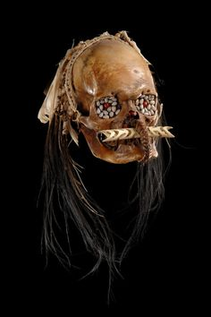 """Papua New Guinea, Asmat bone, polished, the lower jawbone tightly attached to the skull with a woven rattan band, the eye-sockets filled with beeswax and inlaid with the grey seeds of Job's-tear grass (""""Coix lacryma-jobi""""), red seeds of the crab's eye vine"""