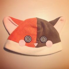 A two-tone cat beanie/plushy hat! It's made out of soft, kind of stretchy polar fleece! The blush marks and nose are made out of felt, and is securely hot glued on. The eyes are black buttons, and are also securely affixed with hot glue.    The hat would fit on a head with an approx. circumferenc...