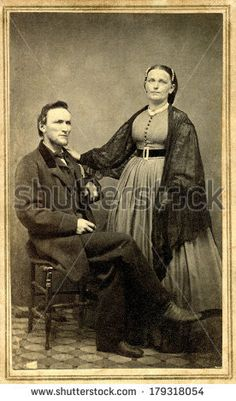 USA - CONNECTICUT - CIRCA 1865 A vintage cartes de visite photo of pioneer couple. Wife is standing and husband sitting. She is dressed in hoop skirt. Photo from Civil War Victorian era. CIRCA 1865