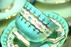 Soft turquoise teacup and saucer. Floral band, gold trim.