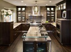 Deep chocolate brown cabinets with crown molding add a traditional touch to this contemporary kitchen design. Glass cabinetry inserts and a glass bartop help keep the room light and fresh.     Drury Design Kitchen & Bath Studio  Glen Ellyn, IL