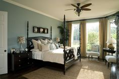 A gorgeous bedroom with light blue walls, white crown molding and dark hardwood floors. Click to see our master bedroom makeover tips!