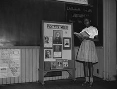"Girl at Monroe School (Washington, D.C.) is seen reading a book entitled ""Poems with Power."" She is standing next to bulletin board with the title ""Poetry Week,"" May 1947."