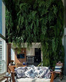 Acostumada a viver em casa, a moradora deste apartamento não abria mão de ter plantas na varanda. Mas o espaço teria que acomodar também os móveis. A solução da arquiteta Selma de Sá Moreira foi aproveitar o pé-direito duplo para um jardim vertical