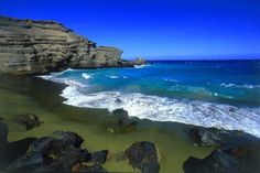 Green Sand Beach (Papakolea), Hawaii.  The sand really is green. The ridged mound is the remains of an olivine cinder cone, Pu'u o Mahana (an extension of Mauna Loa), that has eroded to make the beach. Olivine is a green mineral deposited along the coast by the volcano.