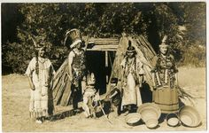 Postcard (black and white; Real Photo); a Native Californian family (Miwok?) posing in front of a tule dwelling with baskets; they all wear traditional clothing and accessories; she wears a basketry hat; California, USA.  Printed