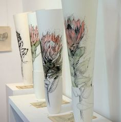 Hermien Van Der Merwe; These drawings of various Proteas are made in mixed media on paper.  They are displayed in ceramic vases.  The stem of the flower is drawn onto the unglazed vase with graphite that is fired into the ceramic.  The inside of the vase is glazed and can also be used for fresh flowers, if the client prefers to have the drawing framed.