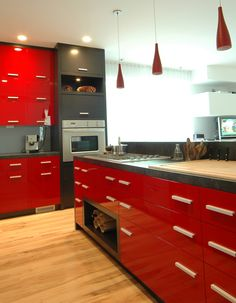 This modern style kitchen blends graffiti black and high gloss red finish with sleek doors, handles and a complimentary stone top. Stunning results created a kitchen that reflects this families modern day needs. www.legacyoriginals.com
