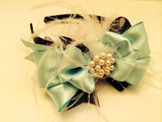 A black headband is adorned with marabou feathers, a black organza bow topped with a famous blue satin bow. The center than holds a beautiful pearl and rhinestone piece. We are crazy in love with this one!