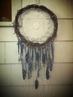 Made this dream catcher from an old grapevine wreath, my Grandmother's crocheted doily, denim strips, and feather patches.