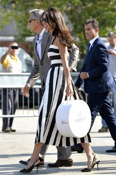 En route to Italy for her weekend of wedding festivities, Alamuddin already looked the part of Mrs. Clooney in this Dolce & Gabbana striped dress, signature oversized sunglasses, and hatbox.