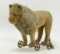 "Sold For $ 375   Antique Steiff mohair lion on cast iron wheels.  The button in the ear, (Knopf Im Ohr in German) indicates that this lion was made in Germany between 1925 and 1935.  Good to fair condition.  Losses to mohair.  This piece has a growler, but it is currently not functional.  Tail is partially separated from the body, and also has a break in the lower 3"" of the tail.  Excellent candidate for professional restoration, as this pi"