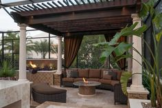A custom wooden pergola sits atop a cozy lounge area with an outdoor sofa framed by elegant curtains in rich brown fabric. An exciting fire table with glass tiles and a nearby fire/water bowl add warmth to the luxurious ambiance of this outdoor living space.
