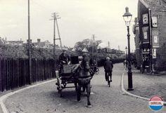 Arnhem: Het noordelijke uiteinde van de Spoorwegstraat bij de spoordijk, gefotografeerd in 1934. Op de spoordijk komt de stoomtrein vanaf station Velperpoort richting station Arnhem aanrijden. Achter de spoordijk links is onder meer het dak van het toenmalige Imelda Kinderhuis aan de Sonsbeeksingel te zien.
