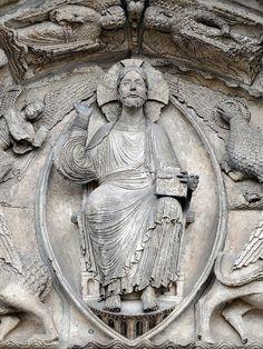 """""""Christ en gloire dans une mandorle"""" - L'implantation du Christ dans une mandorle sur le tympan de la porte d'une église révèle le symbolisme du passage de l'extérieur de l'église vers l'intérieur de l'église, de l'espace profane à l'espace sacré, et préfigure ainsi le passage des vivants du monde terrestre au monde céleste. Autour du Christ, on peut apercevoir, tronqués par le cadrage de la photographie, les symboles des quatre Évangélistes - Cathédrale de Chartres, France."""