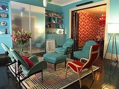 The blue-green on the chair and the walls along with the red fabric on the chairs and the flower pattern on the wall create a split complementary color scheme in this room.