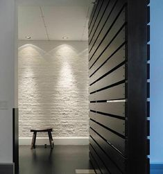 A SoHo Loft as seen on Remodelista. Wood screen meets well lit brick wall.