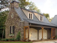 Stonework and colonial 6/6 windows, shed roof dormers with siding following the roof slope (classic colonial), arched carriage-house garage doors, square trellis at ends shed roof ends, window planter box, faux fireplace (its the round window in the gable that gave it away, also that its a garage), standing-seam metal roof, round metal downspouts, real working shutters.