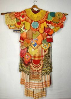 Real women wear a robe of doilies, dish cloths, hot pads, aprons, and dish towels.