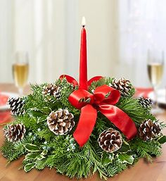 They're all about Christmas traditions, from hanging stockings to making popcorn garlands. Create a new, lasting tradition with this fragrant evergreen centerpiece arrangement, hand-decorated with pinecones, looped red ribbon and a festive red taper candle for a little extra merry.