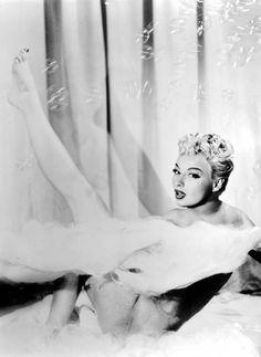 Burlesque dancer Lili St. Cyr on stage in her see-through bathtub c. 1950's