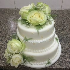 Work wedding cake. Love the Ferne and white rose flower arrangement..