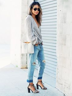 Julie Sarinana of Sincerely Jules wears an oversized sweater, boyfriend jeans, t-strap heels, round sunglasses, and a white bucket bag
