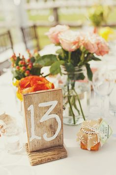Centerpiece and table number with a splash of orange.