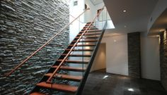 """Custom staircase with metal risers, wood treads and handrail, and 1/2"""" glass inserts."""