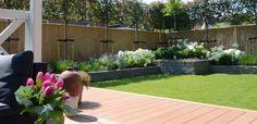 Mooi uitzicht op de tuin | composiet (kunststof) vlonder & bamboe tuinschermen op de achtergrond als schutting (erfscheiding).